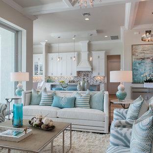 Idées déco pour un salon bord de mer de taille moyenne et ouvert avec un mur beige et un sol en bois clair.