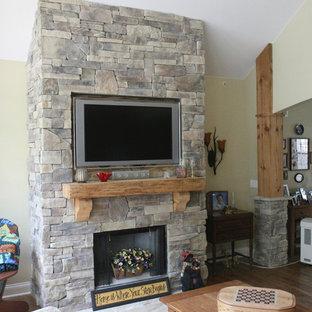 Modelo de salón abierto, clásico, de tamaño medio, sin televisor, con paredes beige, suelo de madera oscura, chimenea de esquina, marco de chimenea de piedra y suelo marrón