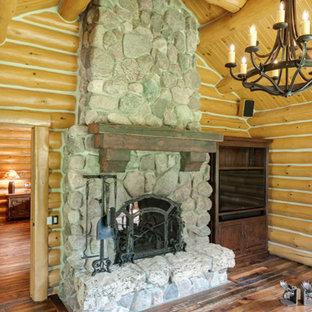 ミネアポリスの大きいラスティックスタイルのおしゃれな独立型リビング (無垢フローリング、両方向型暖炉、石材の暖炉まわり、埋込式メディアウォール) の写真