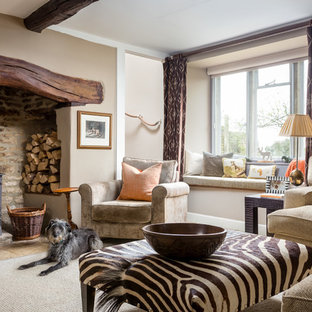 This is an example of a rustic formal living room in Gloucestershire with beige walls, a wood burning stove and beige floors.