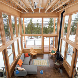 Ispirazione per un grande soggiorno design stile loft con pavimento in cemento, stufa a legna, cornice del camino in metallo e nessuna TV