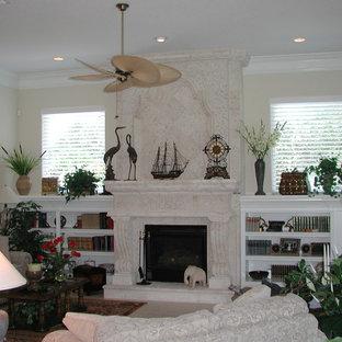 Imagen de biblioteca en casa abierta, clásica, de tamaño medio, con paredes beige, suelo de baldosas de porcelana, chimenea tradicional, marco de chimenea de piedra y televisor en una esquina