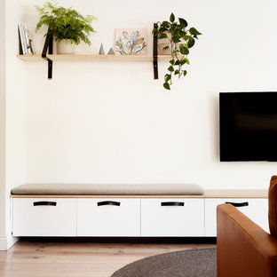 Imagen de salón abierto, escandinavo, pequeño, con paredes blancas, suelo de madera clara, televisor colgado en la pared y suelo blanco