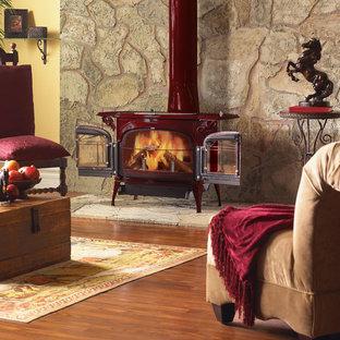 Réalisation d'un salon sud-ouest américain de taille moyenne et fermé avec un mur jaune, un poêle à bois, un manteau de cheminée en métal, aucun téléviseur, un sol marron, une salle de réception et un sol en bois brun.