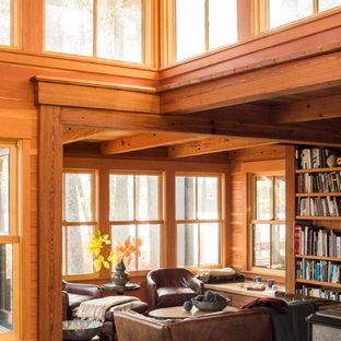 Imagen de biblioteca en casa abierta, rural, pequeña, sin televisor, con suelo de madera en tonos medios, estufa de leña, marco de chimenea de hormigón y suelo marrón