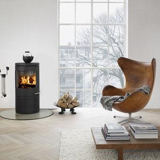 Imagen de salón para visitas abierto, ecléctico, de tamaño medio, sin televisor, con paredes beige, estufa de leña, suelo de madera clara y marco de chimenea de metal