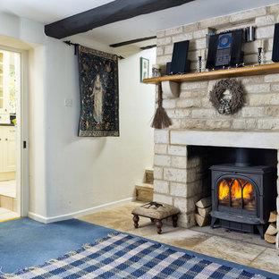 Foto de salón cerrado, campestre, de tamaño medio, con paredes blancas, moqueta, estufa de leña, marco de chimenea de piedra y suelo azul