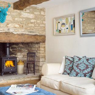 グロスタシャーの小さいトラディショナルスタイルのおしゃれな独立型リビング (白い壁、無垢フローリング、薪ストーブ、石材の暖炉まわり、テレビなし、茶色い床) の写真