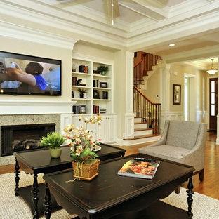 Foto di un grande soggiorno chic aperto con pareti beige, parquet scuro, camino classico, cornice del camino in pietra e TV a parete