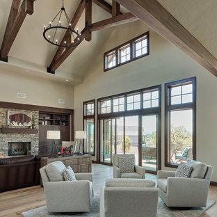 Idées déco pour un salon craftsman ouvert avec un mur gris, un sol en bois clair, une cheminée standard, un manteau de cheminée en pierre, un téléviseur dissimulé et un sol gris.