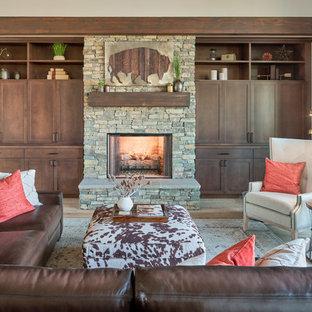Ispirazione per un soggiorno american style aperto con pareti grigie, parquet chiaro, camino classico, cornice del camino in pietra, TV nascosta e pavimento grigio
