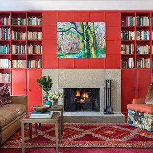 Immagine di un grande soggiorno classico aperto con libreria, pareti rosse, camino classico, parquet chiaro, cornice del camino in cemento e nessuna TV