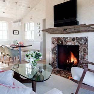 Imagen de salón abierto, marinero, pequeño, con chimenea tradicional, televisor colgado en la pared, paredes blancas, suelo de madera clara y marco de chimenea de piedra