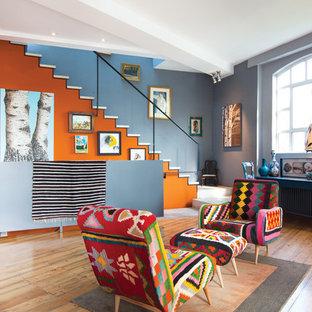 Eklektisk inredning av ett allrum med öppen planlösning, med ett finrum, flerfärgade väggar och mellanmörkt trägolv