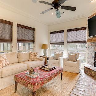 Стильный дизайн: парадная гостиная комната среднего размера в стиле современная классика с белыми стенами, кирпичным полом, угловым камином, фасадом камина из кирпича, телевизором на стене и красным полом - последний тренд