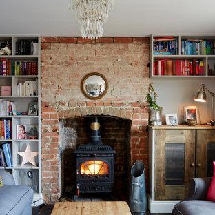 Inredning av ett eklektiskt litet vardagsrum, med ett bibliotek och en öppen vedspis
