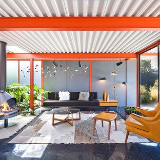 Modelo de salón para visitas vintage, sin televisor, con paredes grises, estufa de leña, marco de chimenea de metal y suelo negro