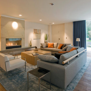 Inspiration for a large modern living room in London with white walls, light hardwood flooring, a ribbon fireplace, no tv and brown floors.