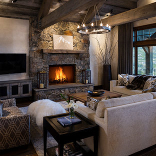 This is an example of a country living room in Other with beige walls, dark hardwood floors, a stone fireplace surround, a wall-mounted tv and a standard fireplace.