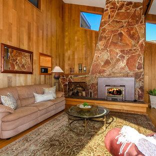 シアトルの大きいビーチスタイルのおしゃれなLDK (無垢フローリング、薪ストーブ、石材の暖炉まわり) の写真