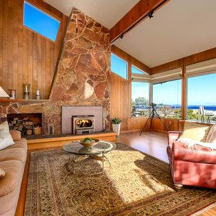Ejemplo de salón abierto, marinero, grande, con suelo de madera en tonos medios, estufa de leña, marco de chimenea de piedra, paredes marrones y suelo marrón