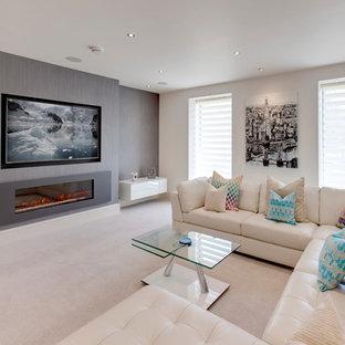 Idee per un grande soggiorno moderno chiuso con angolo bar, pareti grigie, moquette, camino classico, TV a parete e pavimento beige