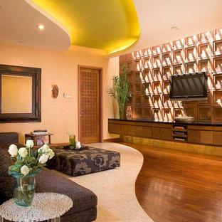 Foto di un soggiorno bohémian con pareti beige, TV a parete e pavimento multicolore