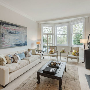 This is an example of a traditional living room in London with carpet, a standard fireplace and no tv.
