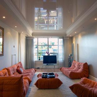 Esempio di un soggiorno design di medie dimensioni e aperto con pareti beige, pavimento in legno massello medio, nessun camino e TV autoportante