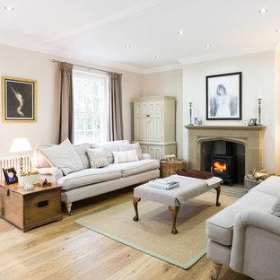 Imagen de salón para visitas cerrado, de estilo de casa de campo, de tamaño medio, sin televisor, con paredes beige, estufa de leña y suelo de madera clara