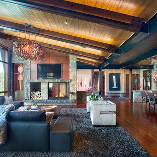 Foto på ett rustikt allrum med öppen planlösning, med bruna väggar, mellanmörkt trägolv, en dubbelsidig öppen spis, en spiselkrans i sten, en väggmonterad TV och brunt golv