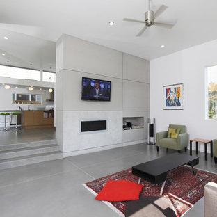 シアトルの中くらいのモダンスタイルのおしゃれな独立型リビング (コンクリートの床、フォーマル、白い壁、横長型暖炉、コンクリートの暖炉まわり、壁掛け型テレビ、グレーの床) の写真