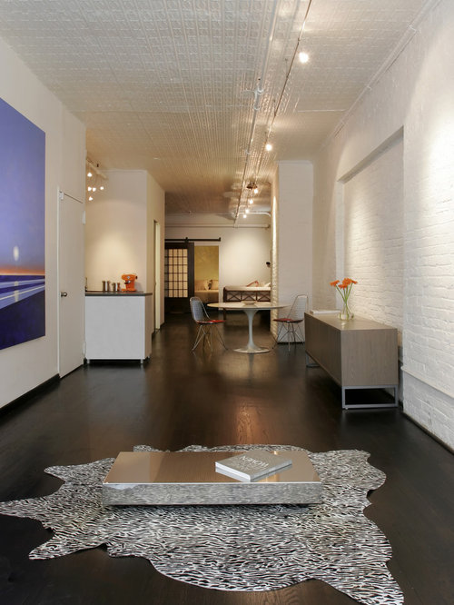 Example Of An Urban Living Room Design In New York With White Walls And Dark Wood