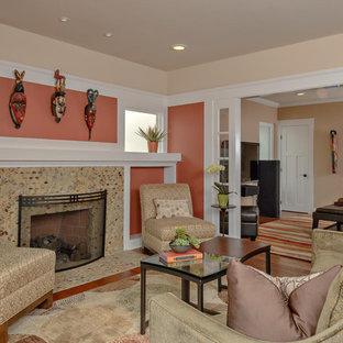 Mittelgroßes Klassisches Wohnzimmer mit gefliestem Kaminsims, oranger Wandfarbe, braunem Holzboden und Kamin in San Diego