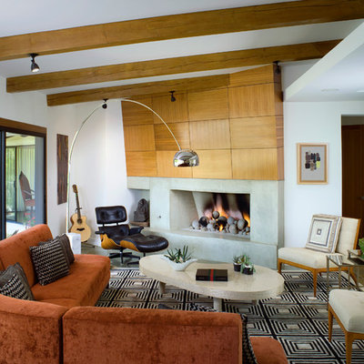 Example of a trendy formal living room design in Los Angeles with white walls, a standard fireplace and a concrete fireplace