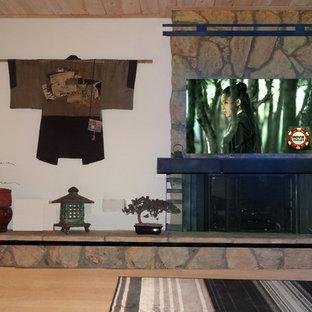 オレンジカウンティの中サイズのアジアンスタイルのおしゃれな独立型リビング (フォーマル、ベージュの壁、竹フローリング、標準型暖炉、石材の暖炉まわり、壁掛け型テレビ) の写真