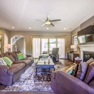 Foto di un grande soggiorno chic aperto con sala formale, pareti grigie, parquet scuro, camino classico, cornice del camino in legno e TV a parete