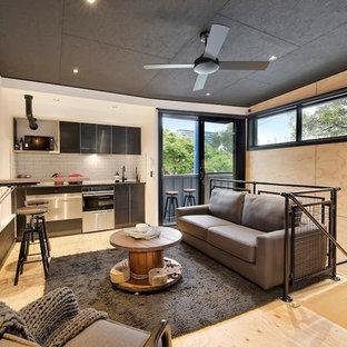 Immagine di un piccolo soggiorno industriale stile loft con pavimento in compensato e TV a parete