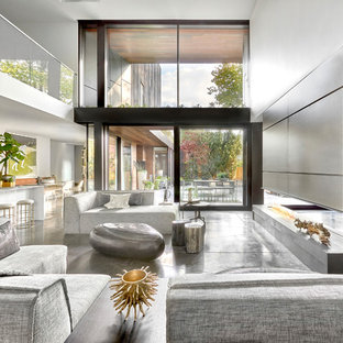 Inspiration for a large contemporary enclosed living room in Chicago with concrete flooring, white walls, a two-sided fireplace, grey floors and a concealed tv.
