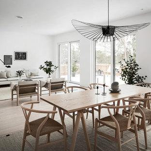 Foto på en skandinavisk matplats med öppen planlösning, med vita väggar och ljust trägolv