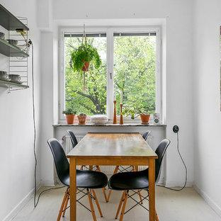 Nordisk inredning av ett kök med matplats, med vita väggar och beiget golv