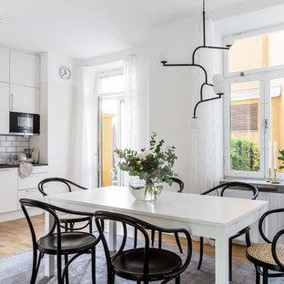 Inredning av ett nordiskt mellanstort kök med matplats, med vita väggar, mellanmörkt trägolv och brunt golv