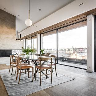 Foto de comedor nórdico, abierto, con paredes blancas, suelo de madera clara, chimenea de doble cara, marco de chimenea de hormigón y suelo gris