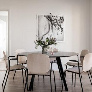Minimalistisk inredning av en separat matplats, med vita väggar, brunt golv och ljust trägolv