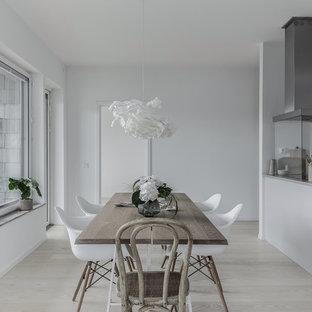 Inredning av ett nordiskt kök med matplats, med vita väggar, ljust trägolv och beiget golv