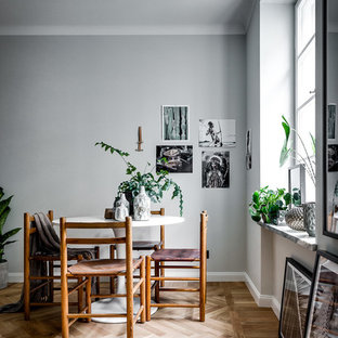 Inspiration for a mid-sized scandinavian light wood floor enclosed dining room remodel in Stockholm with gray walls