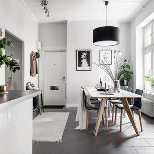 Inredning av ett nordiskt litet kök med matplats, med vita väggar, svart golv och betonggolv