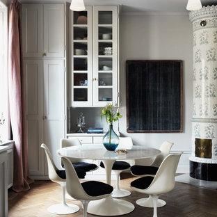 Imagen de comedor de cocina ecléctico, de tamaño medio, con paredes blancas, suelo de madera en tonos medios y chimenea de esquina