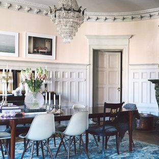 Foto di una grande sala da pranzo aperta verso il soggiorno boho chic con pavimento in legno massello medio, cornice del camino in pietra, pareti arancioni e stufa a legna