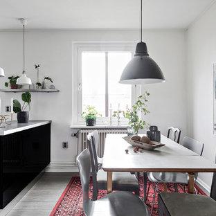 Inredning av ett skandinaviskt kök med matplats, med vita väggar, mörkt trägolv och grått golv